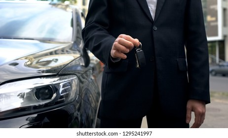 Car buyer holding keys to new vehicle, successful auto purchase transaction