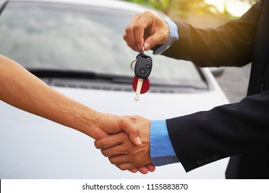 Car buyers are taking car keys from car owners. Buy sell and rent concept