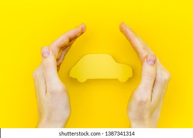 Car buying and insurance concept with car figure in hands on yellow background top view