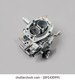 Car carburetor for internal combustion engine for mixing air with a fine spray of liquid fuel on gray background, side view. Automotive parts.