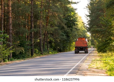 A car carrying a dangerous cargo rides on the road through the forest in the afternoon
