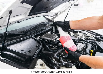 Car in a carwash. Wash with foam in wash station. Carwash. Washing vehicle at the station. Car washing concept. Car detailing. A man cleaning car with foam and brush