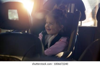 car child seat- smiling toddler girl in her car seat