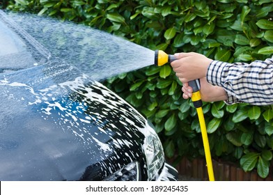 car cleaning - Removing the soap with water, using a garden hose and a spray gun.