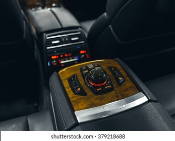 Car climate control. Interior of prestige modern car. Leather comfortable seats. Black cockpit with exclusive wood & metal decoration.
