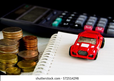car coins and calculator on note book and black  background