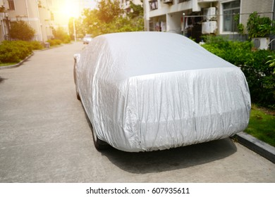 A car with cover sheet for sunlight protection.