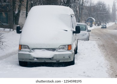 Car covered with fresh white snow in the city. Minibus under the snow. Sleet slush, ice covering on the roads, and southeastern
