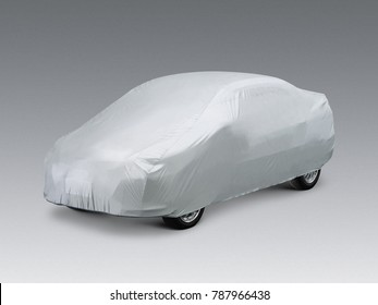 A car covered with a grey cloth, isolated on grey background.