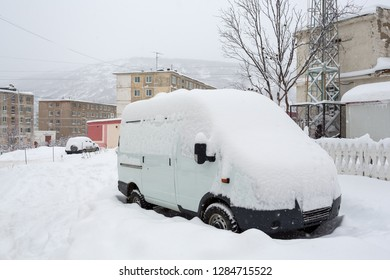 Car covered with snow after a snowfall. Snowdrifts around on the road and in the yard. Snow on the roof and windshield of the car. In the background panel buildings and the hill. Magadan, Russia.