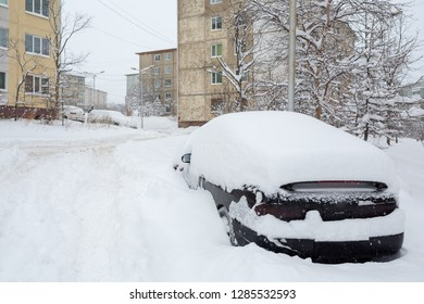 Car covered with snow after a snowfall. Snowdrifts around on the road and in the yard. Snow on the roof and windows of the car. In the background panel buildings. Magadan, Russia.