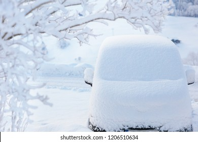 Car covered with snow after winter storm. Vehicle parked snowy tree. Driveway with family car after heavy snow blizzard.