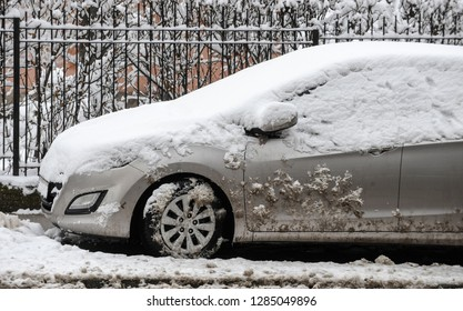 A car covered with snow parked on the street