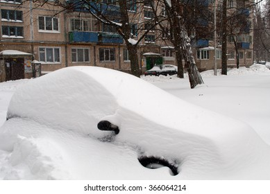 Car covered with snow in the parking after a snow storm