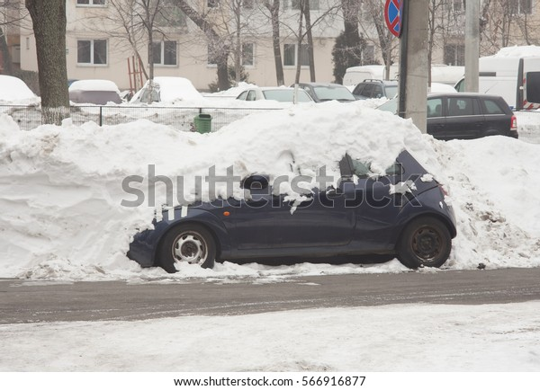 car covered in snow, urban scene in Bucharest city after a winter storm