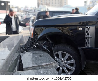 Car crash accident. Luxury car crashed into a stone fence.