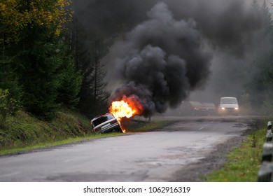 Car crash. Car burning on road. Thick black smoke from car in fire.