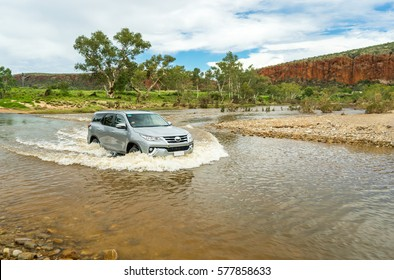 Car crossing a river at Glen Helen, NT Australia. Water is about 60cm high. Rocks and sand laying in the river bed, eucalyptus trees and red cliff in the background.