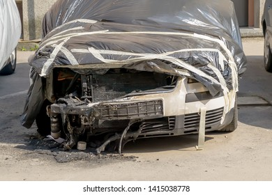 Car damaged by fire. Partially burnt cars covered with a black film on a city street. Front wheels, hood and bumper of a car suffered with a fire. Accident, arson or vandalism.
