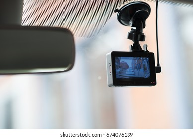 A car dash cam mounted on the front windshield recording the traffic ahead in case of an emergency situation or an accident.