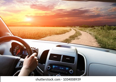 Car dashboard with driver's hand on the black steering wheel against blue sky with clouds