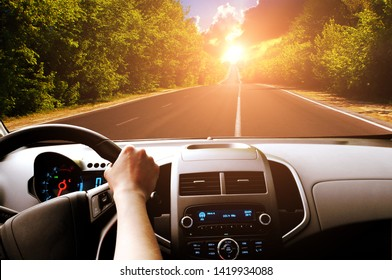 Car dashboard with driver's hand on the black steering wheel and road with green trees against sky with sunset