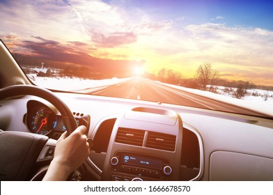 Car dashboard with driver's hand on the black steering wheel against a winter asphalt road in motion and a night sky with a sunset