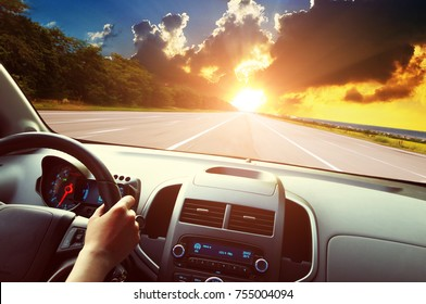 Car dashboard with driver's hand on the black steering wheel against the empty asphalt road and blue sky with beautiful sunset