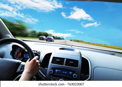 Car dashboard with driver's hand on the black steering wheel against asphalt road and blue sky with clouds