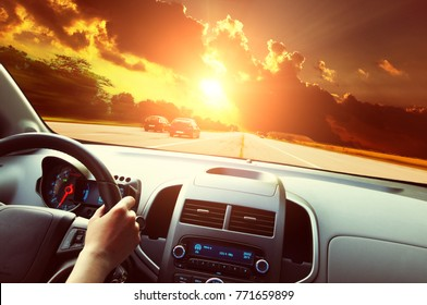Car dashboard with driver's hand on the black steering wheel against road and night sky with sunset