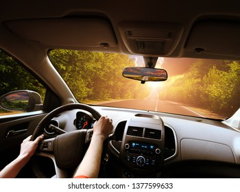 Car dashboard with driver's hands on the black steering wheel and rear view mirrors on a road in motion with green trees against night sky with sunset