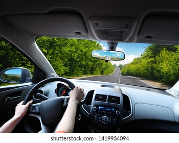 Car dashboard with driver's hands on the black steering wheel and rear view mirrors on a road with green trees against blue sky with clouds