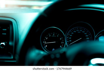 Car dashboard interior view. Car instrument panel with tachometer and speedometer. View from steering wheel to rpm gauge and speed meter. Car engine indicator. Closeup dashboard with auto light.