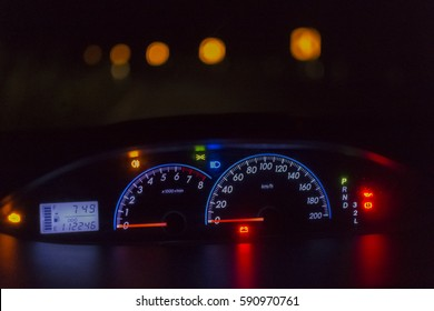 Car dashboard lights  and road background in the  night.Close up.