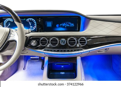 Car dashboard luxury. Beige leather, climate control, speedometer, display, wood decoration & blue ambient light