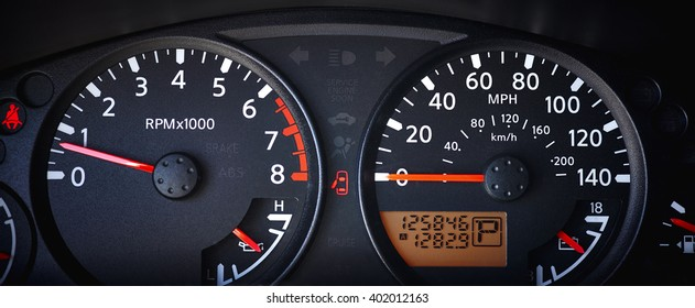 Car dashboard with speedometer, odometer and tachometer and indicator lights