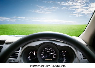 Car dashboard speeds while on green grass and sky. car driving fast