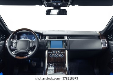 Car dashboard & steering wheel. Interior of prestige modern car. Black cockpit with exclusive wood & metal decoration on isolated white background.