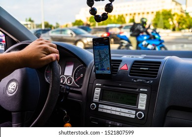 In car dashboard view with smartphone showing Waze maps to show the way thru the city in Bucharest, Romania, 2019