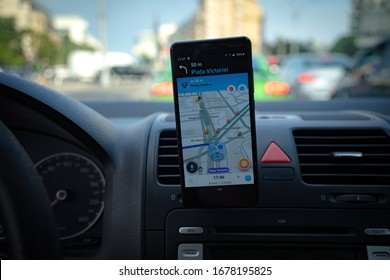 In car dashboard view with smartphone showing Waze maps to show the way thru the city in Bucharest, Romania, 2020
