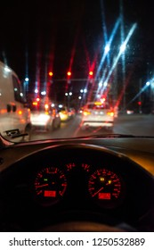 Car dashboard and window at night. Traffic lights