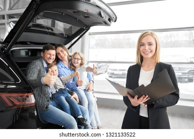 Car dealer, beautiful blonde woman standing, holding folder and posing. Happy family sitting in car trunk, smiling, looking at camera and showing thumbs up, buyers of automobile.