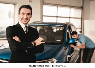 Car Dealer Camera Posing With A Buyer On Background. Cheerful Customer. Automobile Salon. Make A Decision. End Of A Deal. Good Offer. New Buying. Business Trade. Confident Seller. Thumb Up.