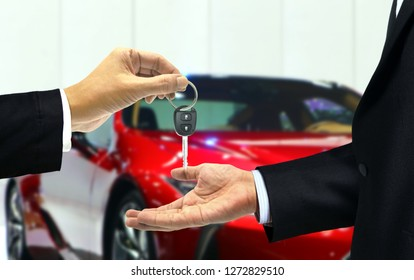 Car dealer and customer car key handover at agent showroom