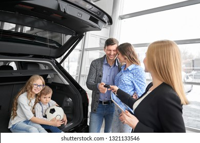 Car dealer of dealership showrrom working with clients, holding folder and giving car keys to buyers of vehicle. Couple standing, posing, daughter and son sitting in car trunk, hugging, smiling.