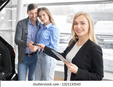 Car dealer giving keys to buyers of automobile, holding folder. Happy pretty couple standing behind, taking keys, smiling. Beautiful blonde woman looking at camera and posing.