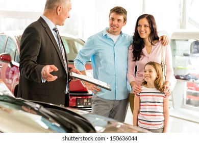 Car dealer offering a car to smiling family