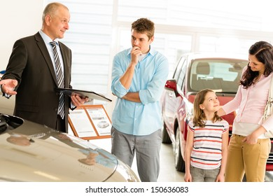 Car dealer offering a vehicle to young couple