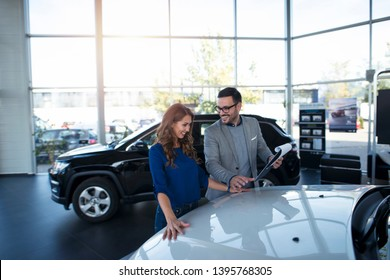 Car dealer presenting new vehicle to the customer. Brand new vehicles. Automobile dealership.