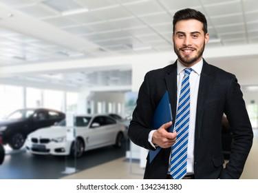 Car dealer smiling in a car saloon